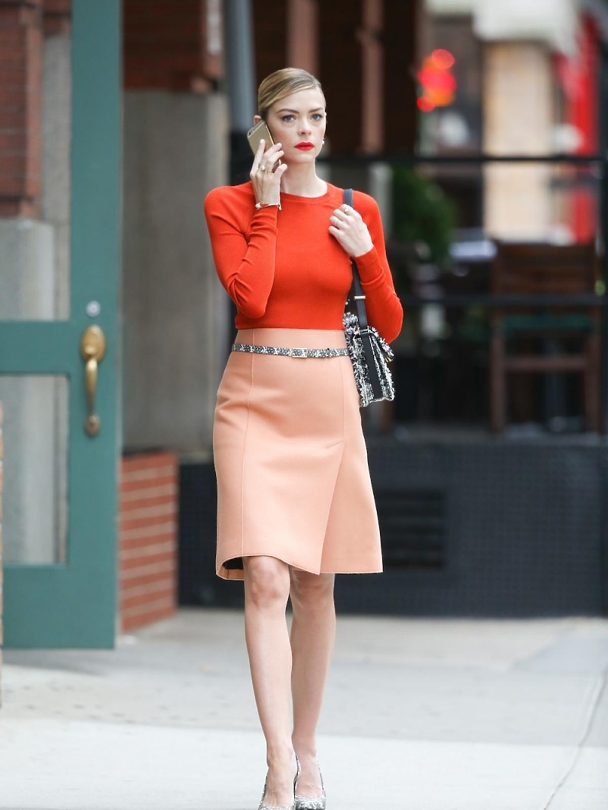 Aktorka Jaime King w bladoróżowej spódnicy i oranżowym topie przechadza się po mieście