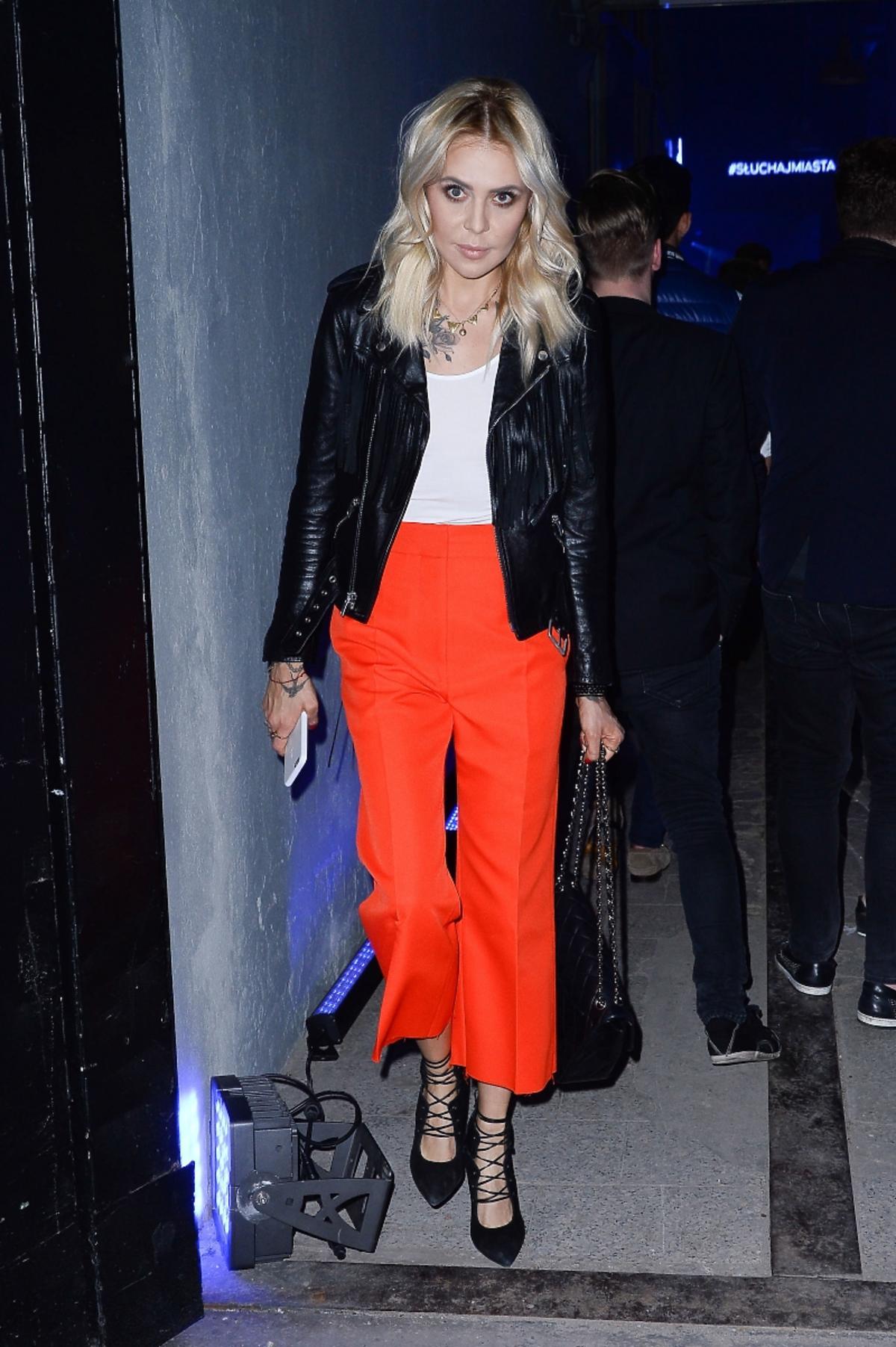 Modna Maja Sablewska w czarnych sandalkach, białym topie, skórzanej kurtce z frędzlami i pomarańczowych spodniach typu culottes