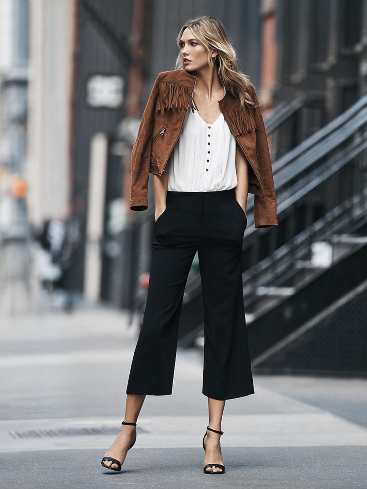 Modna stylizacja Karlie Kloss z zamszową kurtką, czarnymi spodniami culottes i sandałkami z pasków