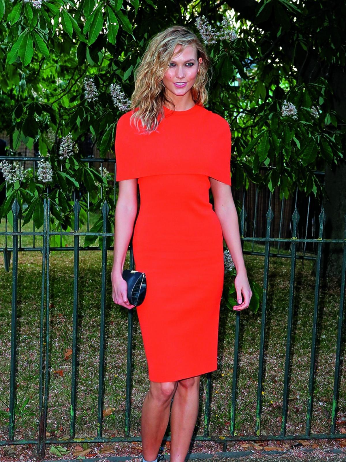 Supermodelka Karlie Kloss w intensywnie pomarańczowej sukience pozuje na imprezie na świeżym powietrzu