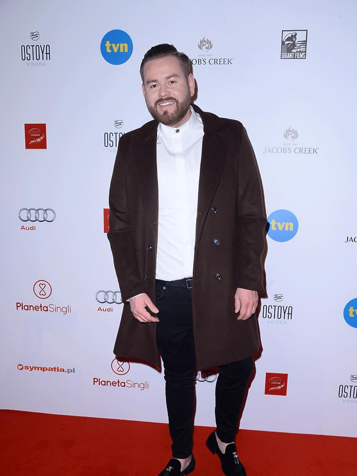 Tomasz Olejniczak w białej koszuli i brązowym płaszczu