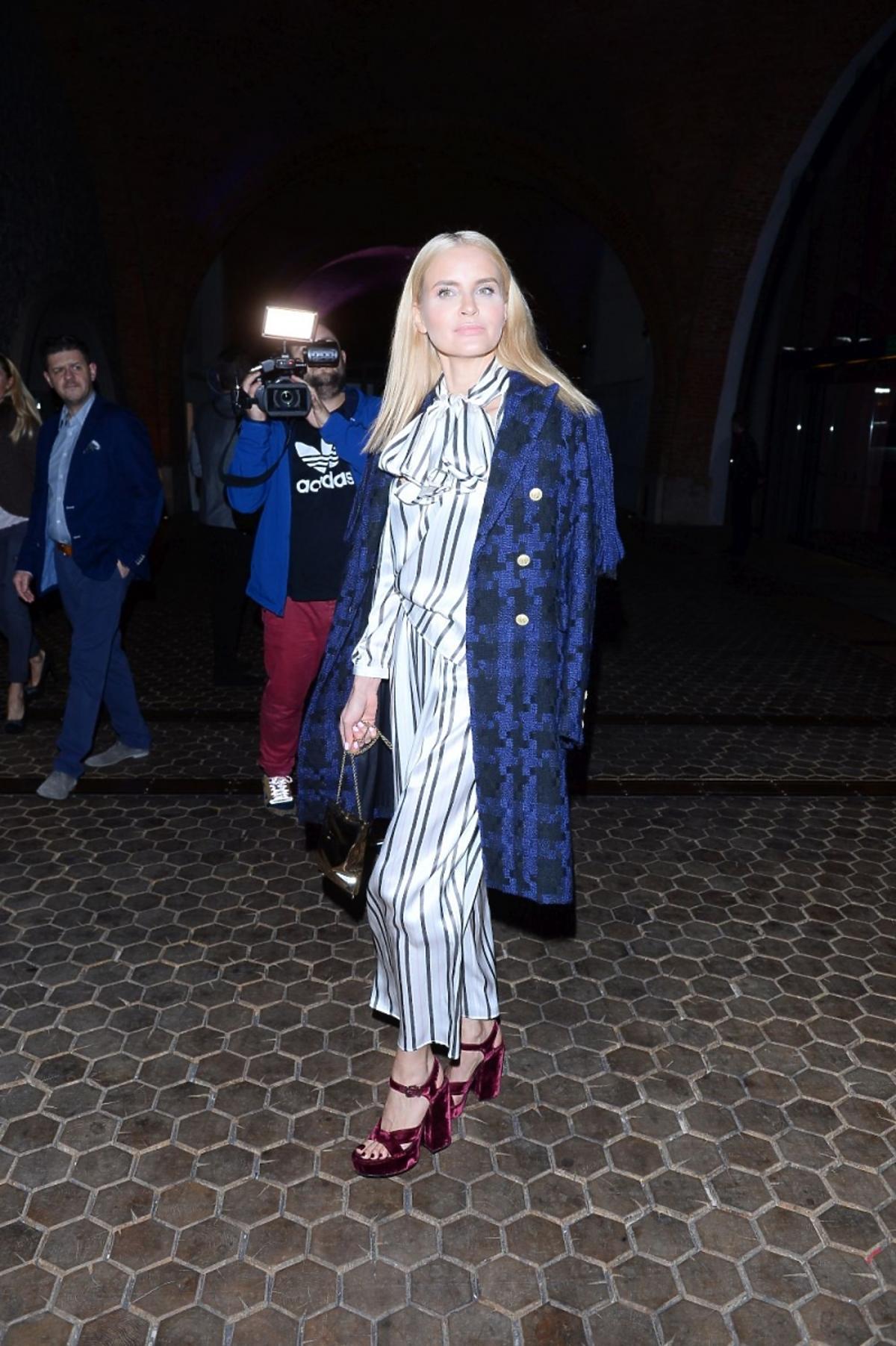 Joanna Horodyńska w czarno-niebieskim płaszczu i kombinezonie