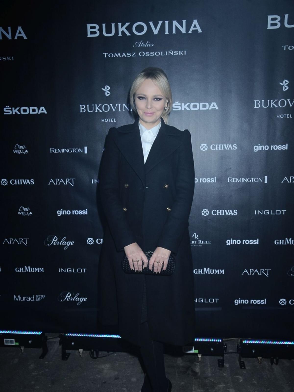 Agnieszka Jastrzębska w czarnym płaszczu i białej koszuli na pokazie Tomasza Ossolińskiego