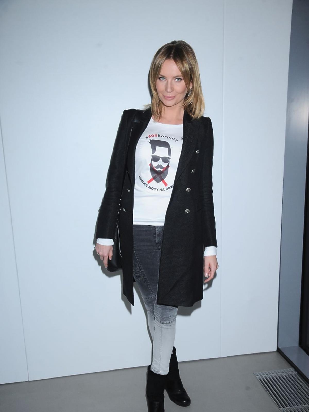 Agnieszka Szulim w czarnym płaszczu, białym T-shircie i szarych spodniach