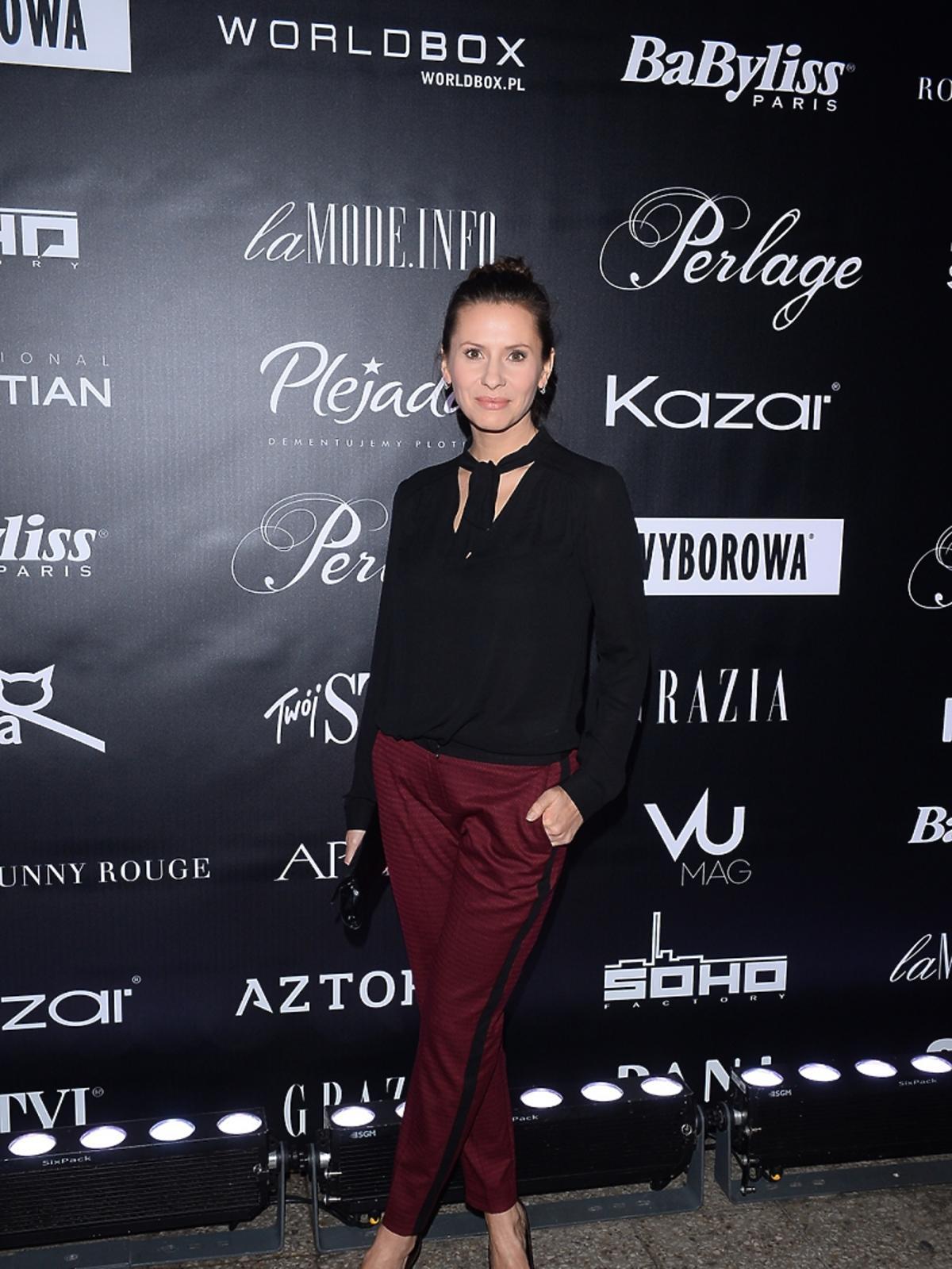 Anna Kerth w czarnej kuszuli i czerwonych spodniach na pokazie mody