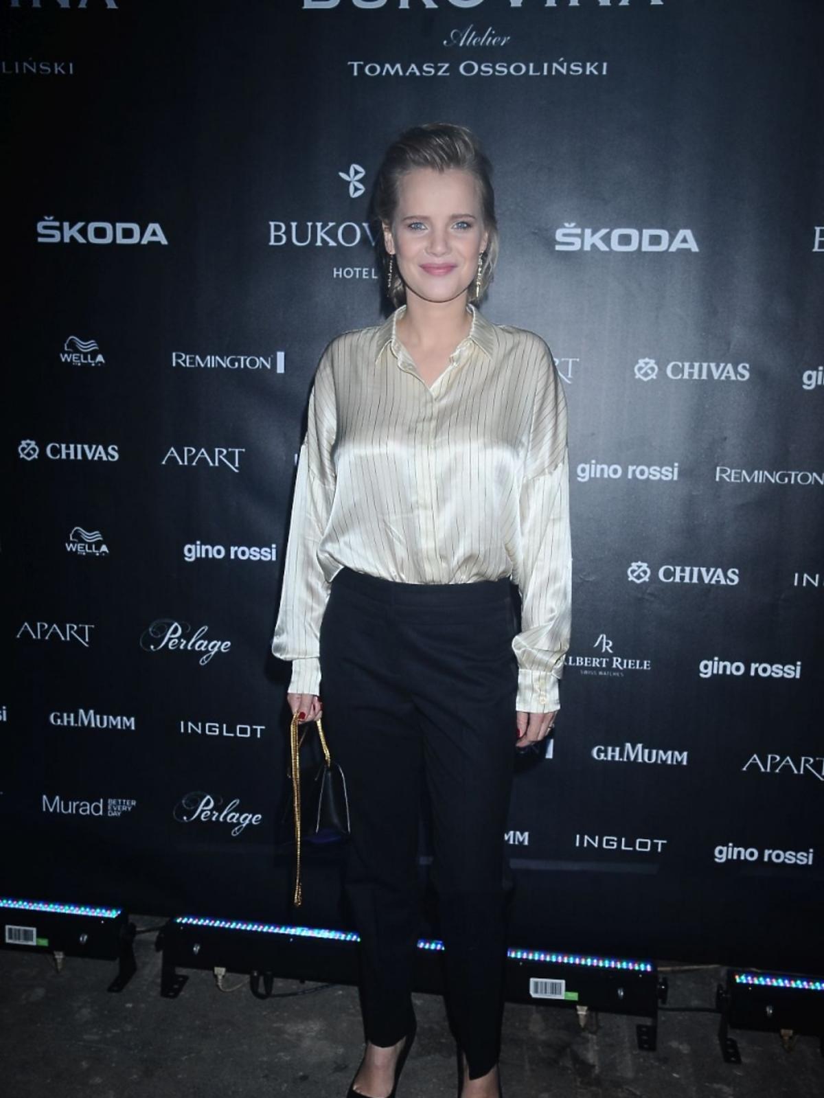 Joanna Kulig w satynowej, złotej koszuli na pokazie Tomasza Ossolińskiego