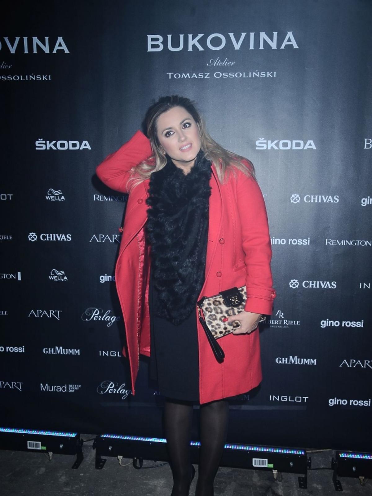Karolina Szostak w czarnej sukience i z torebką w panterkę na pokazie Tomasza Ossolińskiego
