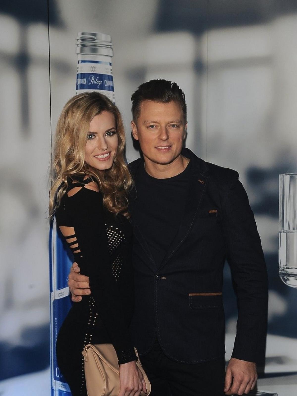 Rafał Brzozowski w czarnej marynarce z dziewczyną Anną Tarnowską pozują do zdjęć na pokazie Tomasza Ossolińskiego