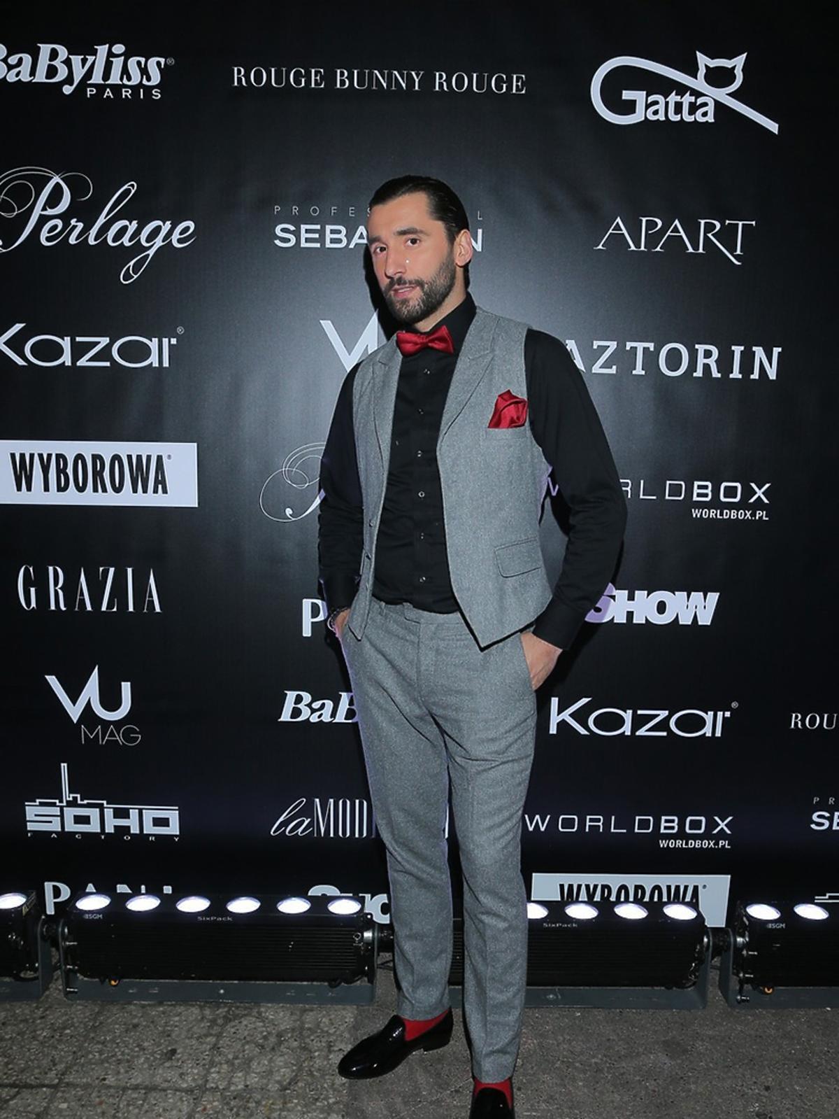 Rafał Maserak w szarym garniturze