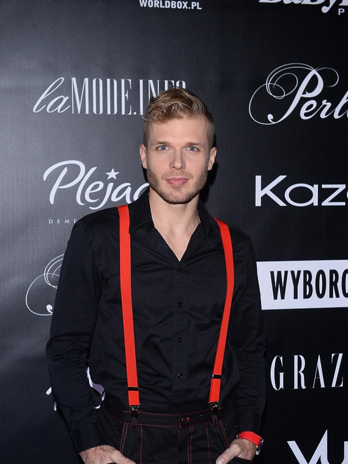 Tomasz Ciachorowski w czarnej koszuli i czerwonych szelkach