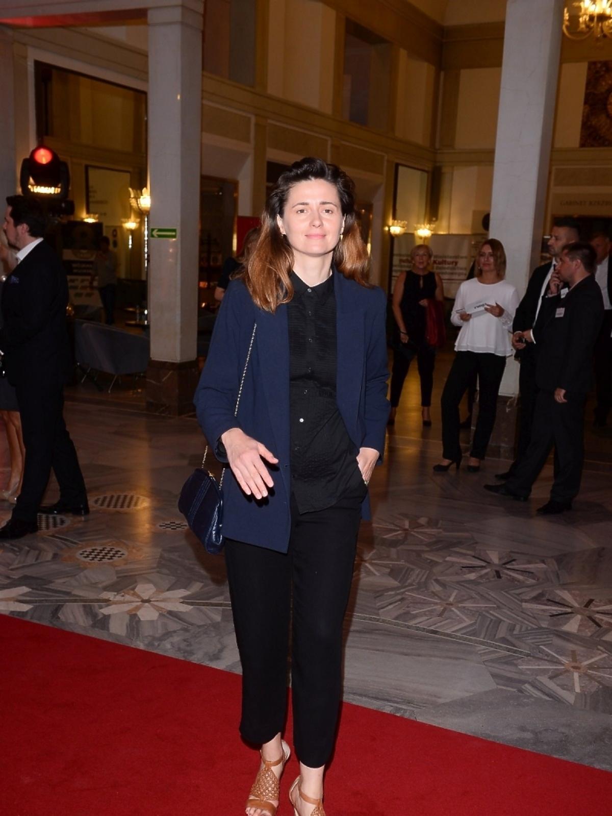 Agnieszka Grochowska w niebieskiej marynarce i czarnych spodniach na czerwonym dywanie