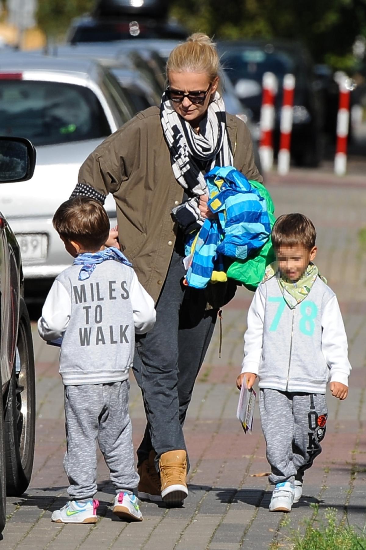 Aneta Zając w kucyku i portowych brazowych butach z synami w dresach na ulicy