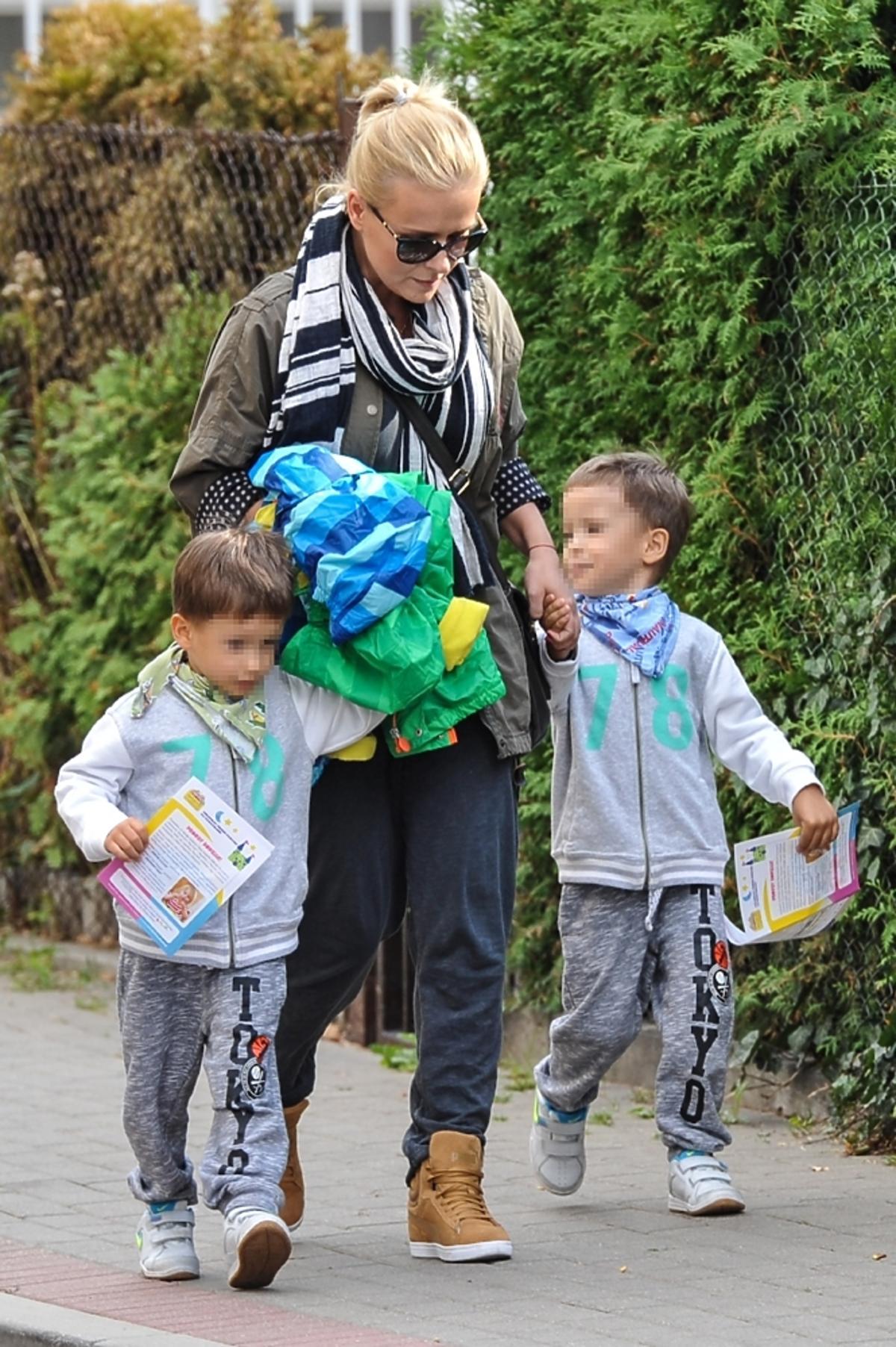 Aneta Zając w szaliku w kratkę z synami w szarych dresach na ulicy