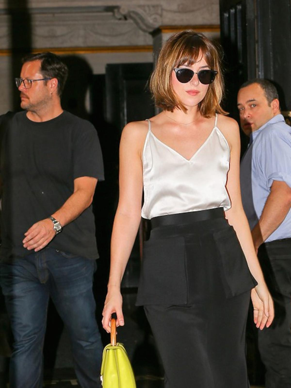 Dakota Johnson w białym topie i czarnych okularach i czarnej spódnicy, czarnych butach i seledynowej torebce