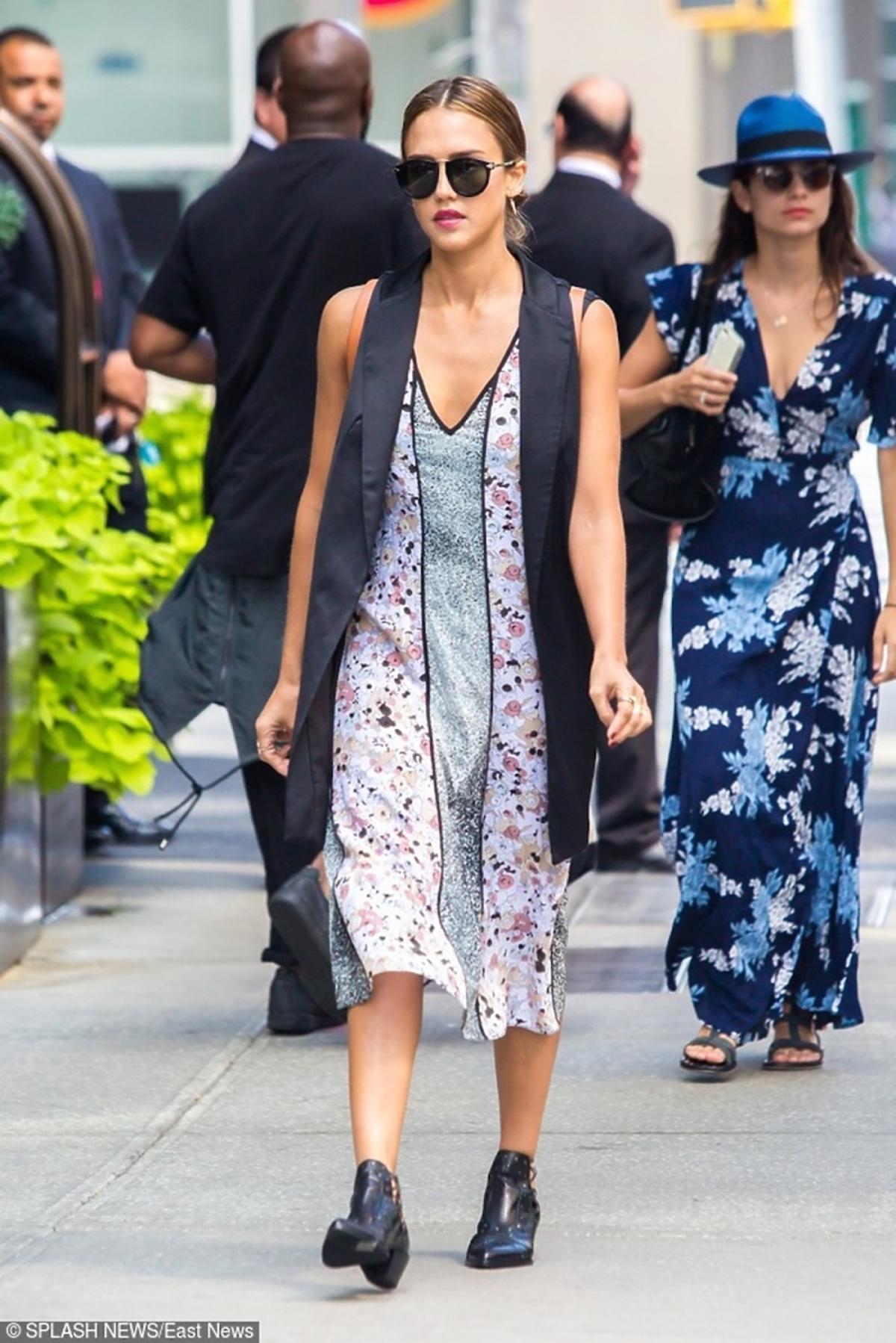 Jessica Alba w czarnej długiej kamiezelce, sukience w kwiaty, czarnych okularach, czarnych botkach na ulicy