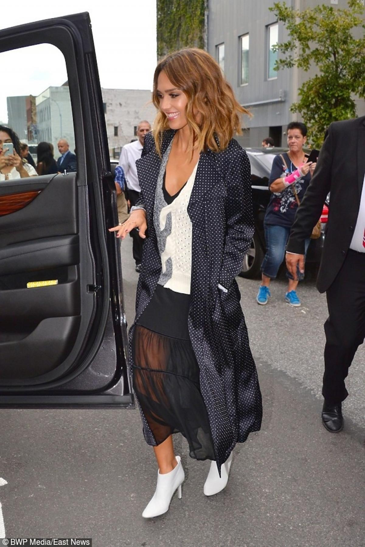 Jessica Alba w czarnej spódnicy, białych botkach, białym swetrze, czarnym płaszczu w białe groszki