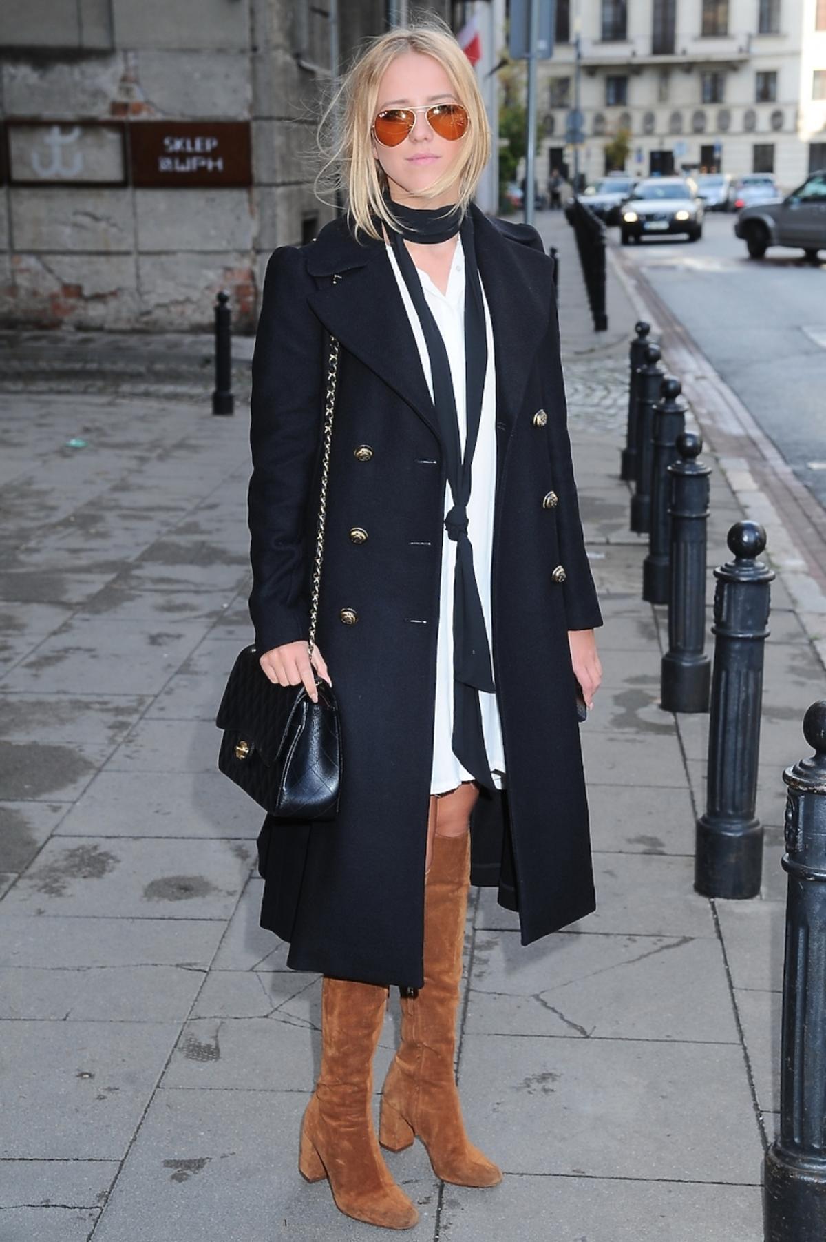 Jessica Mercedes w białek sukience, czarnym płaszczu brązowych kozakach w okularach