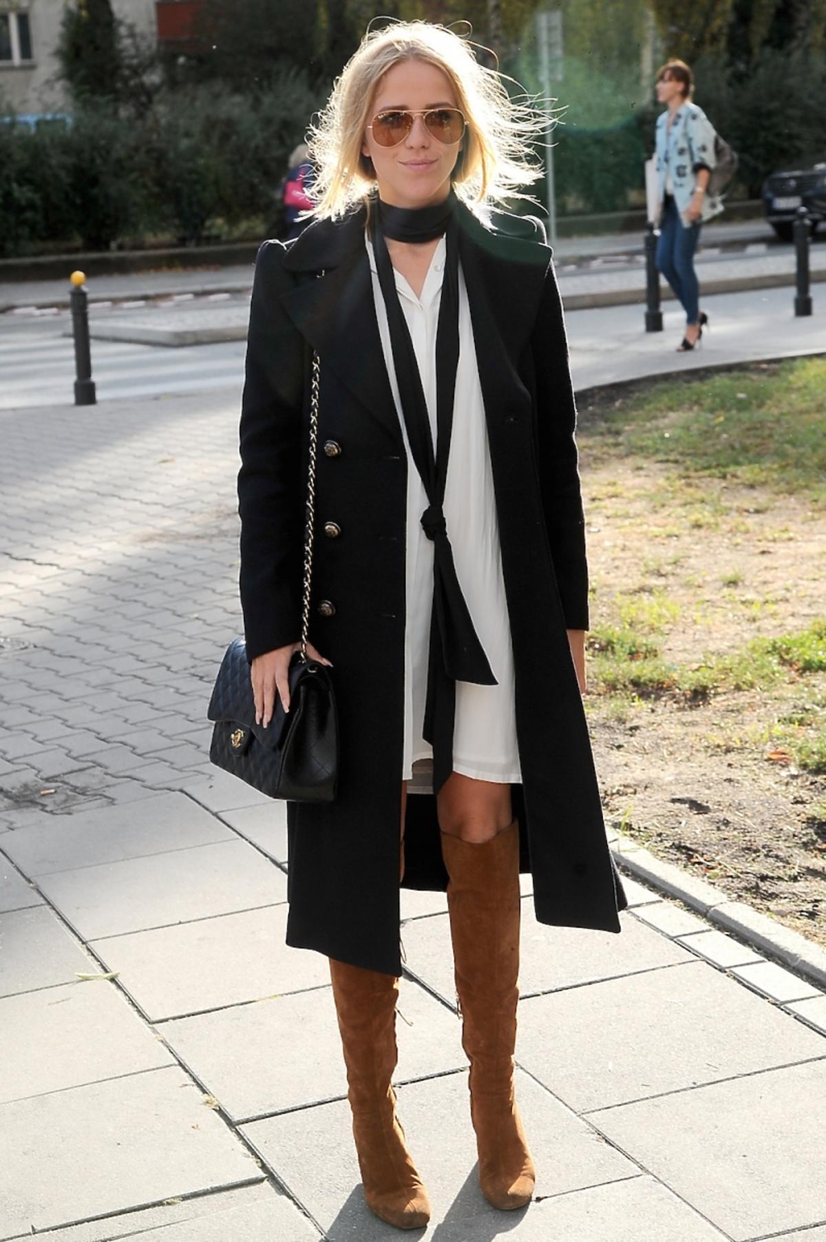 Jessica mercedes w czarnym płaszczu i białej sukience,  brązowych kozakach