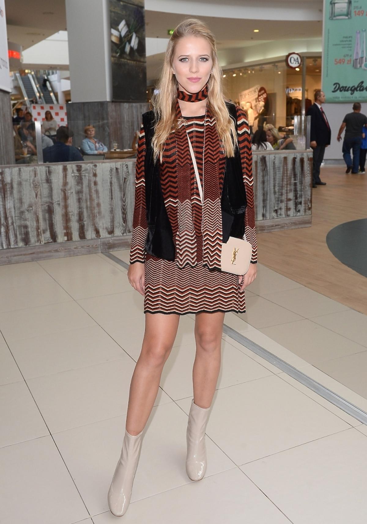 Jessica Mercedes w sukience w kolorowe printy, ciekim szaliku, czarnej kamizelce, beżowych botkach, beżowej torebce na długim pasku