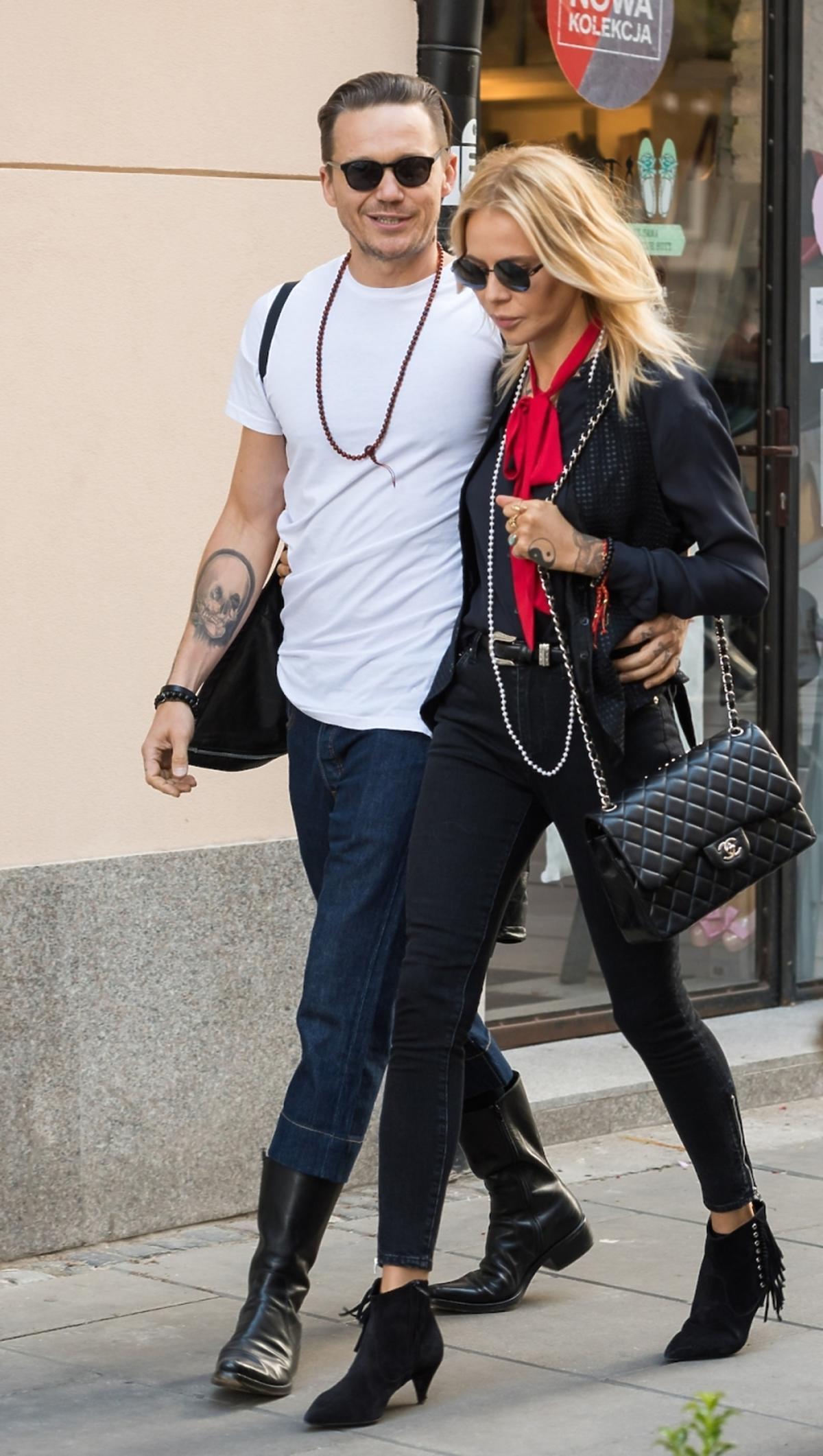 MMaja Sablewska na ulicy ubrana na czarno z czerwonym szalem i czarną pikownątorebką chanel