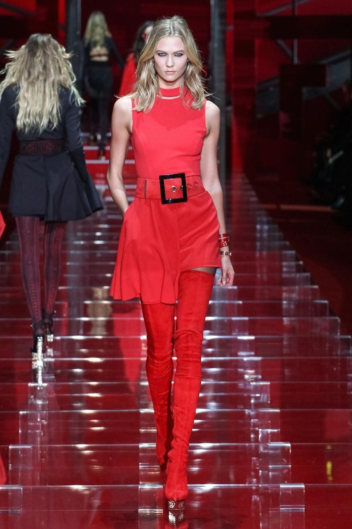 Modelka nna pokazie Versace w czerwonej sukience i czerwonych kozakach