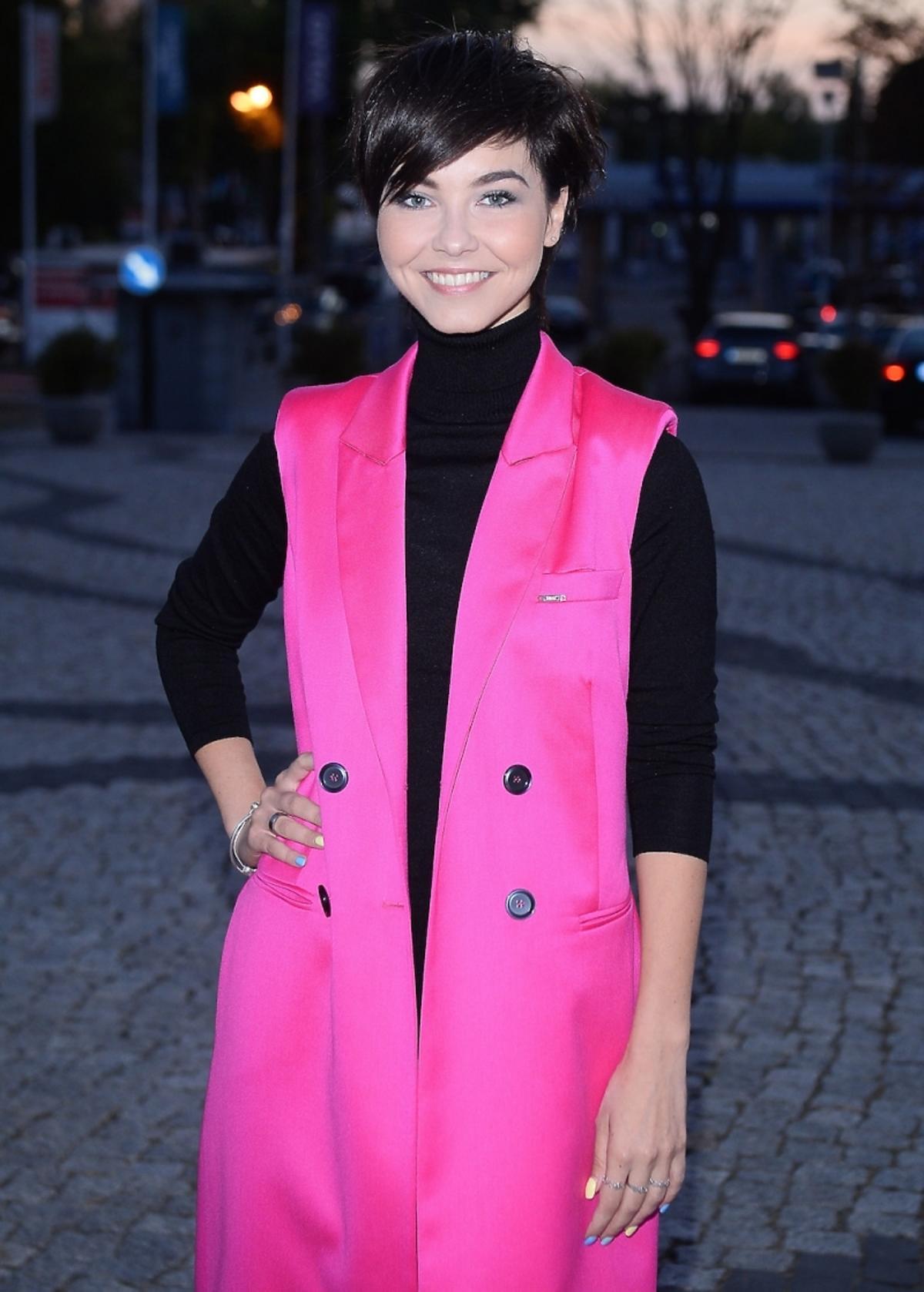 Paulina Drażba w różowej długiej kamizelce marki Simpkle,czarnym golfie, czarnych rurkach