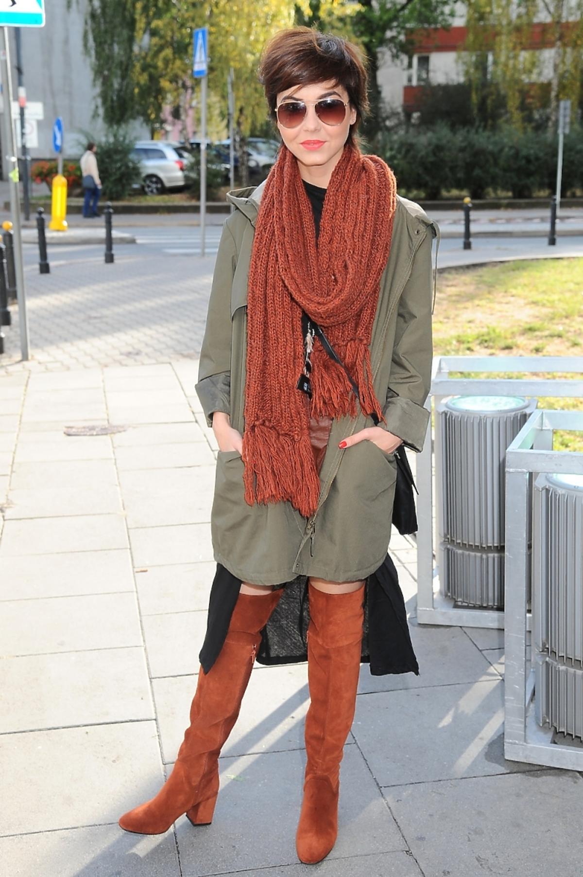 Paulina Drażba w zielonej parce i brązowym szaliku i brązowych kozakach i okularach na ulicy
