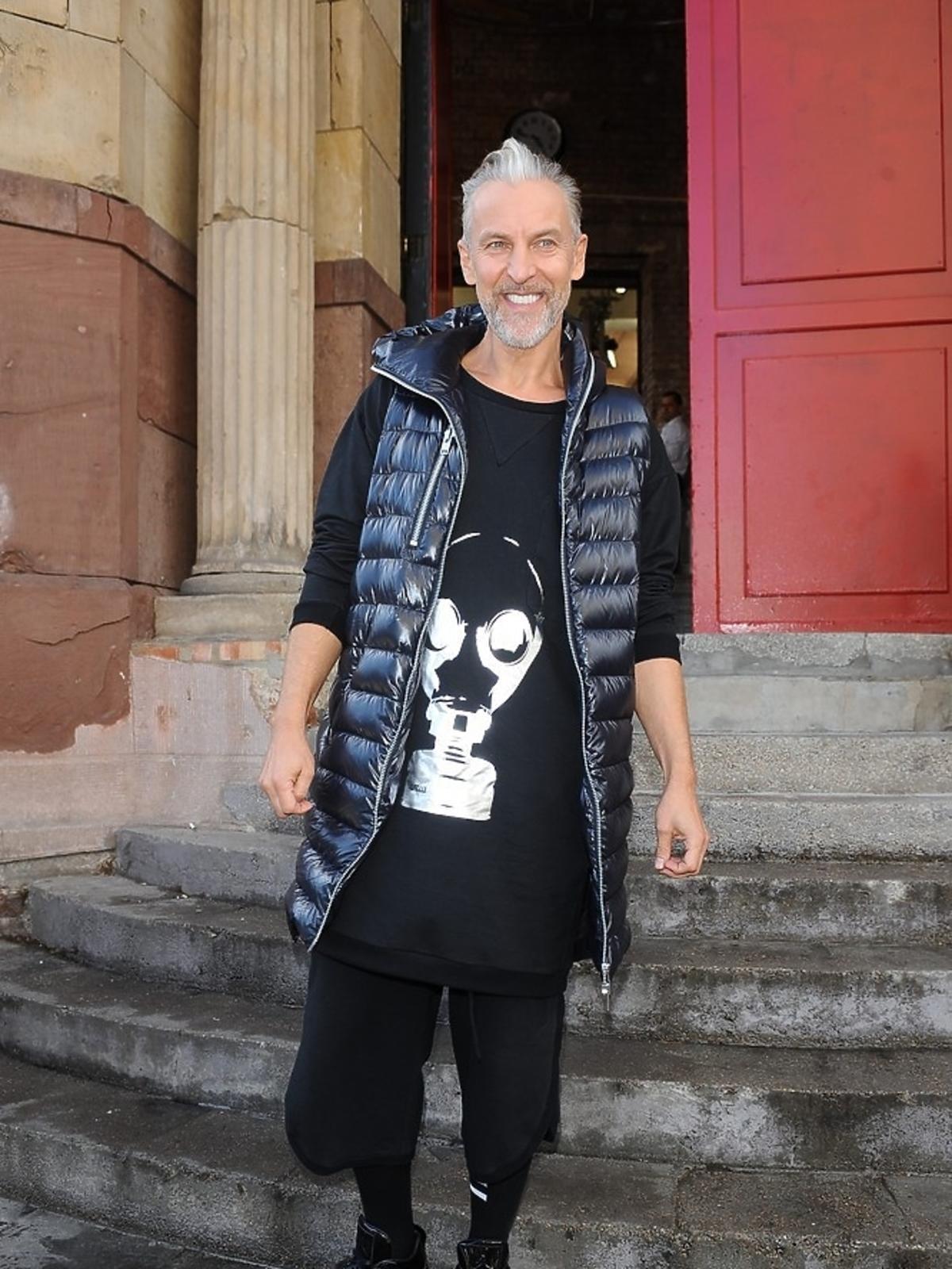 Robert Kupisz w czarnej bluzie ze znaczkiem maski gazowej na ulicy