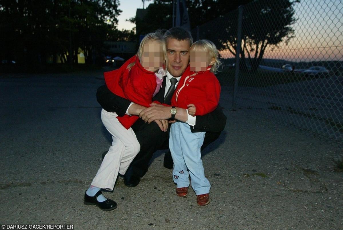 Roman Giertych w garniturze z córkami w czerownych ubrankach