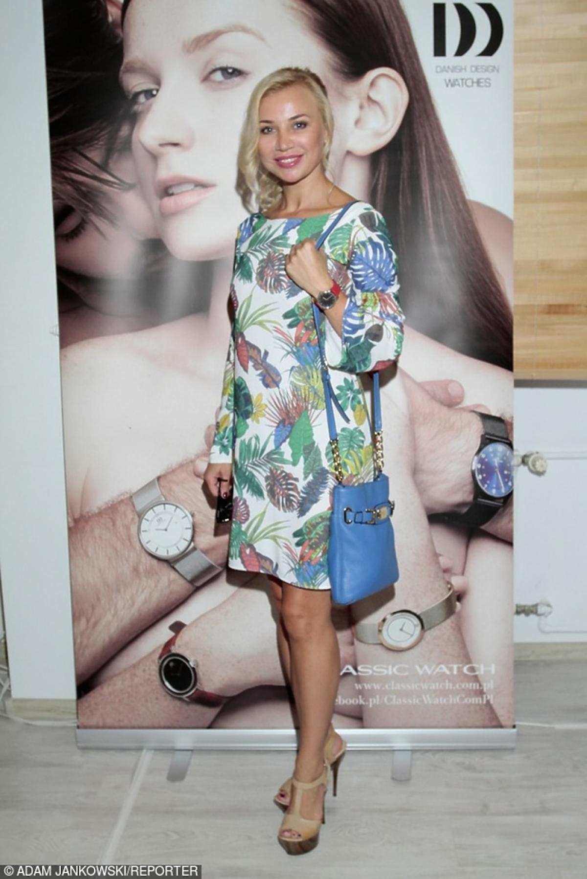 Lidia Kopania w sukience w kolorowe liście z niebieską torbą na pasku i beżowych sandałach na szpilce