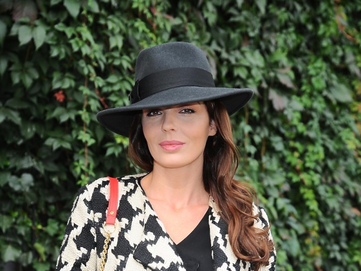 Agnieszka Włodarczyk w poszarpanych dżinsach, czarno-białym płaszczu, z czerwoną torebką w czarnym kapeluszu