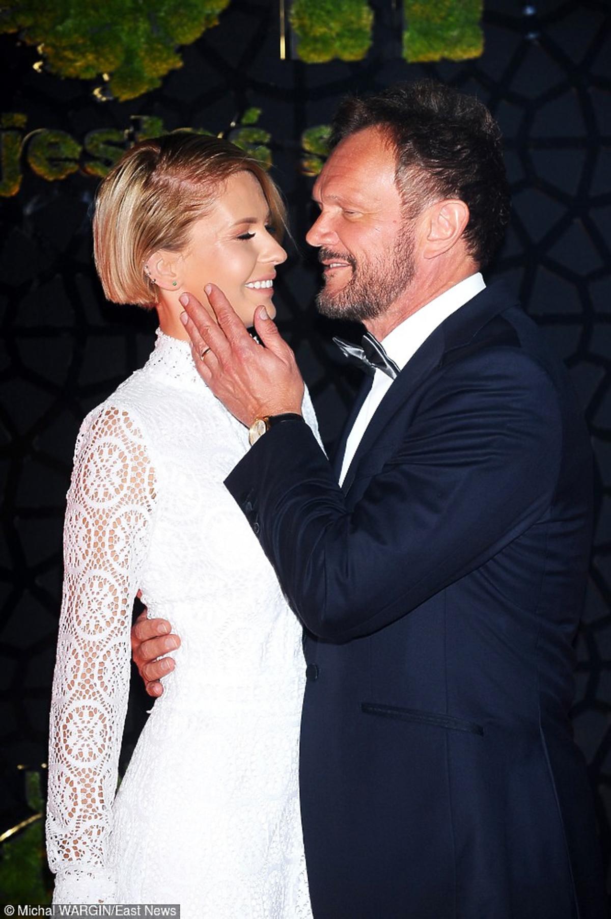 Edyta Zając w białej koronkowej sukni jest przytulana przez męża - Cezarego Pazurę, który jest w czarnym garniturze i dotyka dłonia jej twarzy
