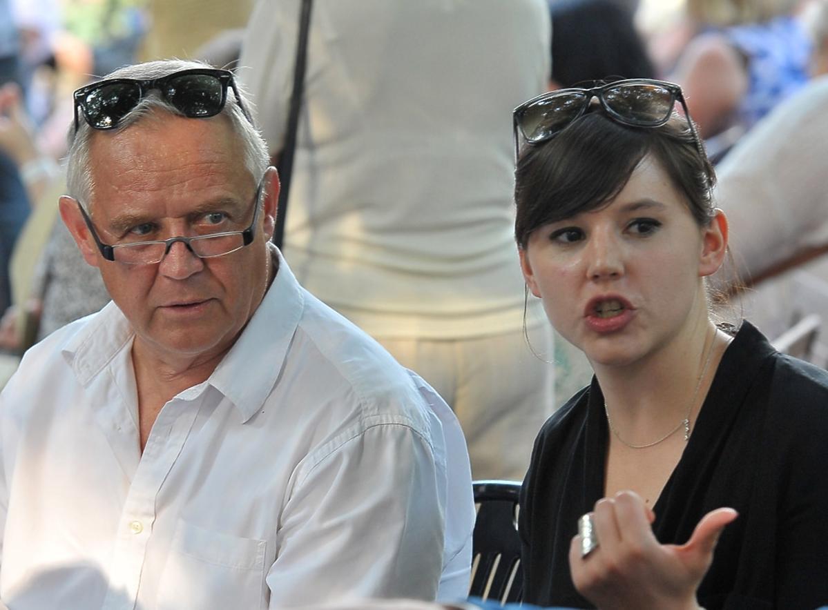 Marek Kondrat w białej koszuli siedzi ze zdziwioną Antoniną Turnau, która ma na sobie czarną bluzkę, obije mają na głowie okulary