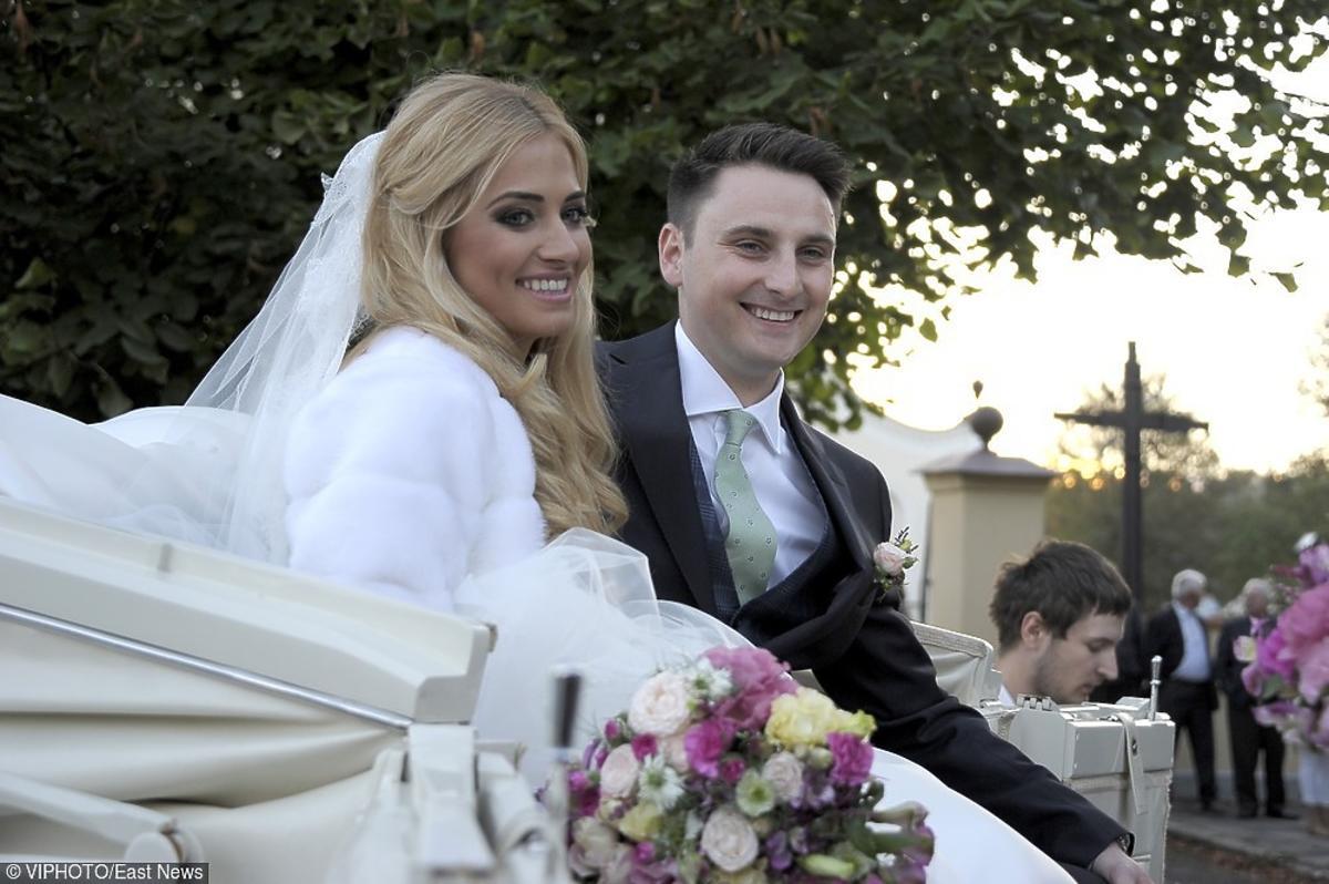 Rozalia Mancewicz w białej sukni ślubnej i welonie, Marcin Jaworski w ciemnym garniturze i zielonym krawacie, jadą dorożką