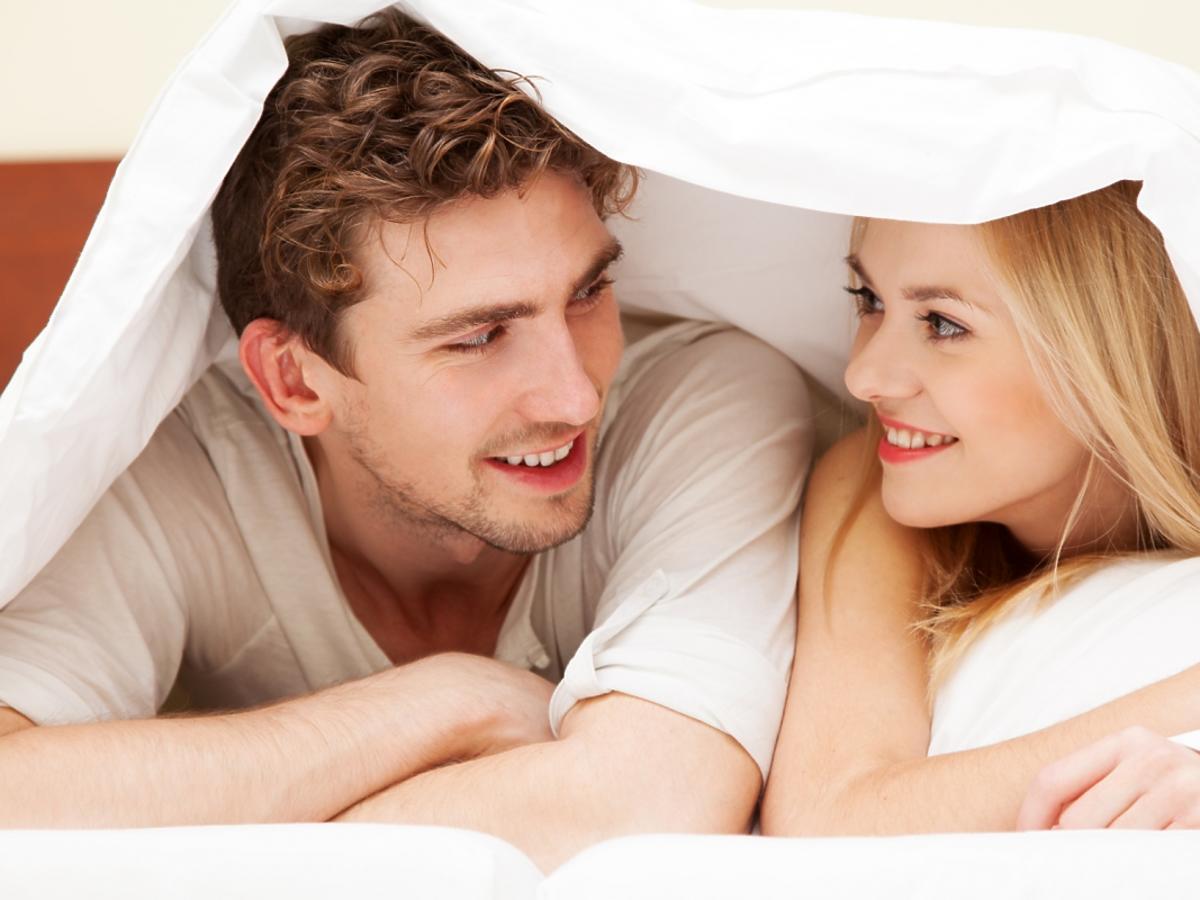 Uśmiechnięta para w łóżku