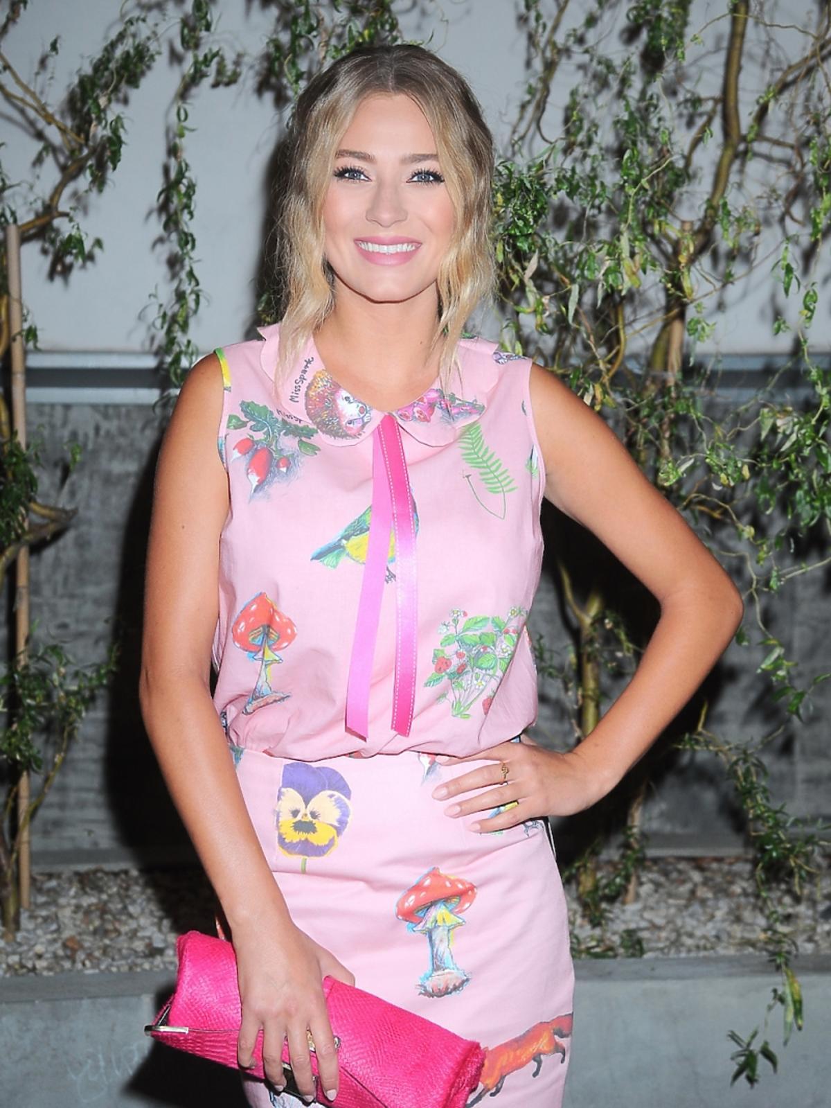 Marcelina Zawadzka w różowej sukience w kolorowe nadruki zwierząt i kwiatów, różowa torebka