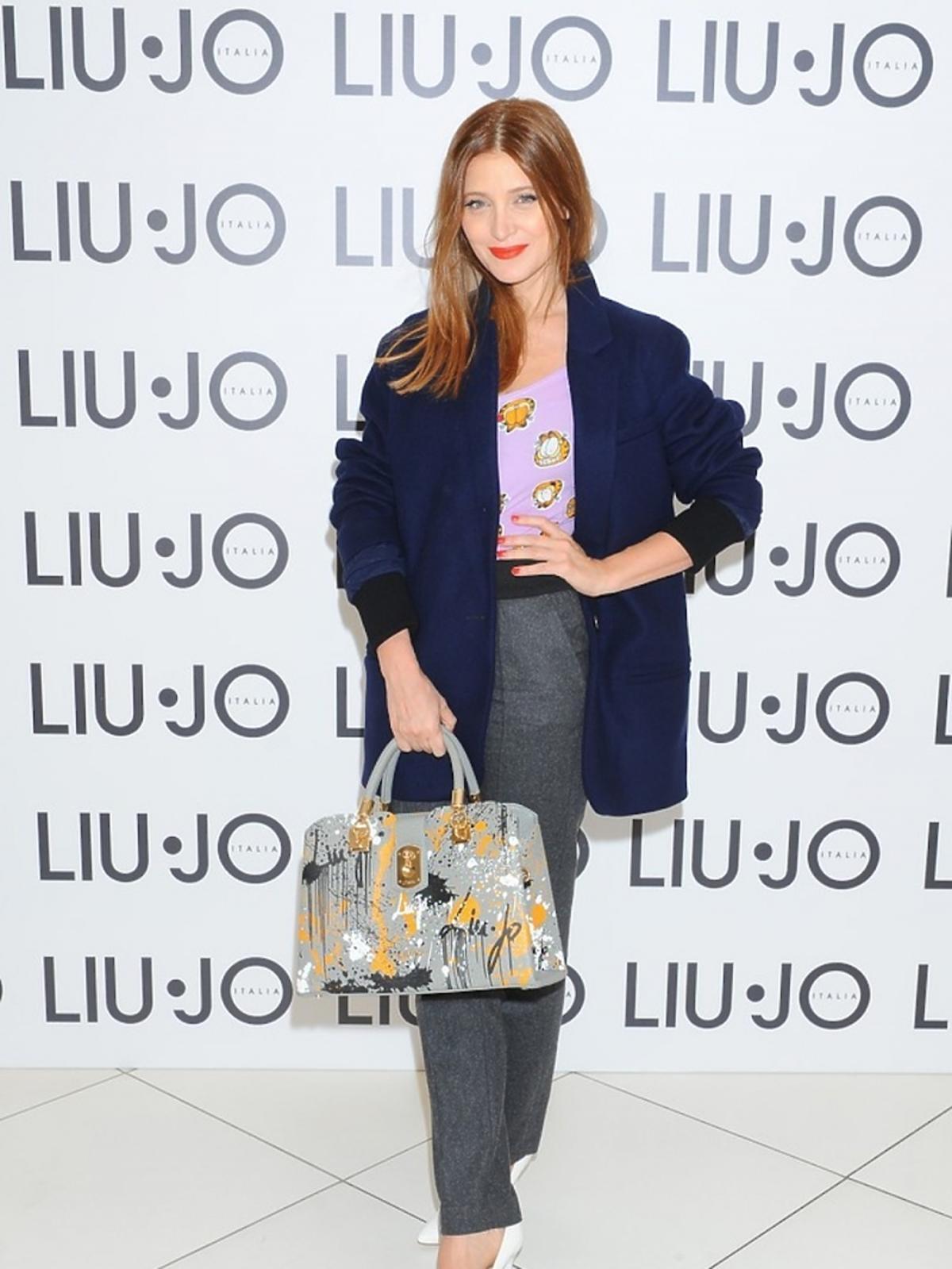 Ada Fijałw szarych spodniach, granatowej marynarce, fioletowym topie w zwiarzaki, białych szpilkach, torbie w malarskie printy