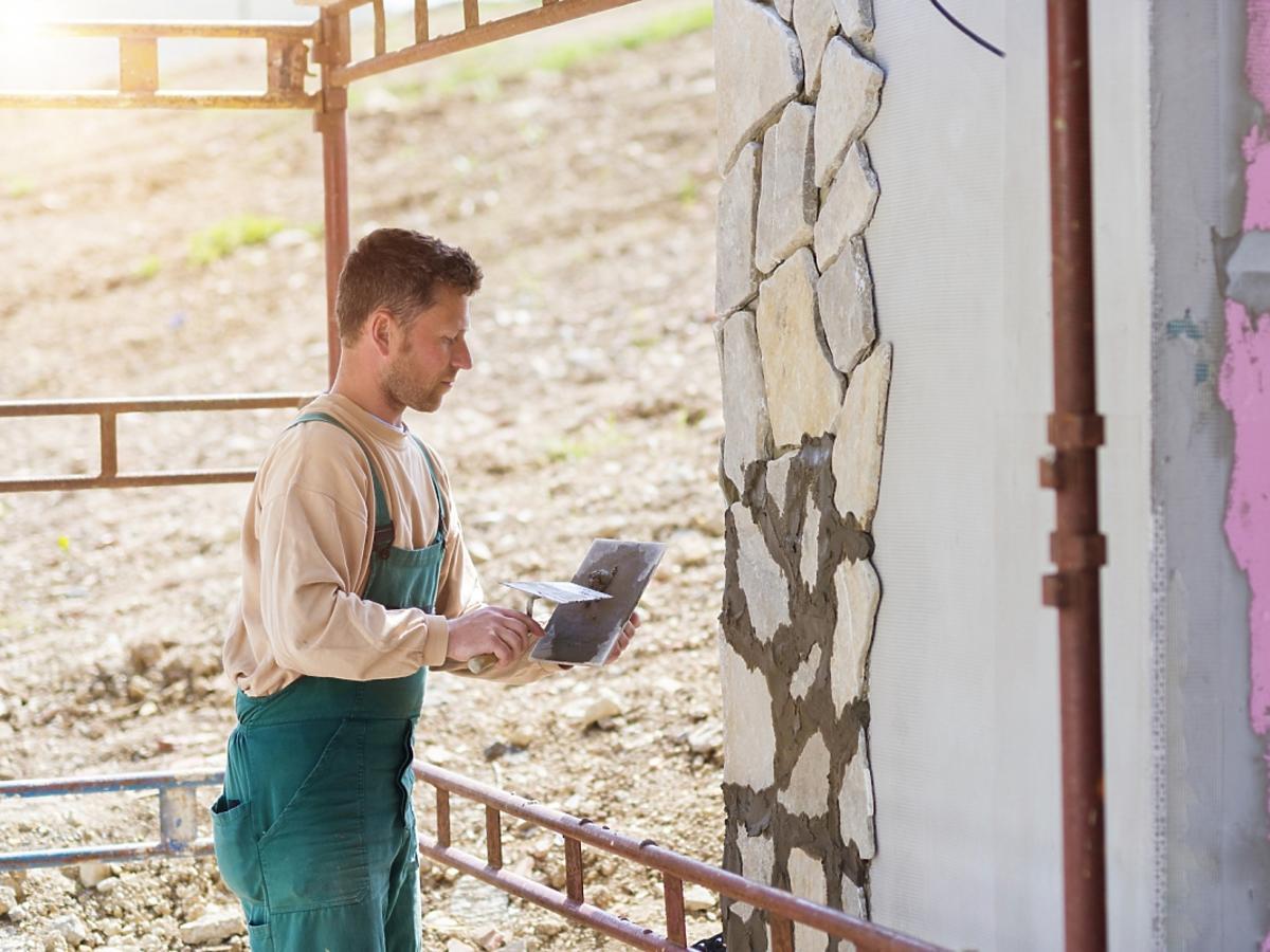 Mężczyzna maluje ścianę na beżowo
