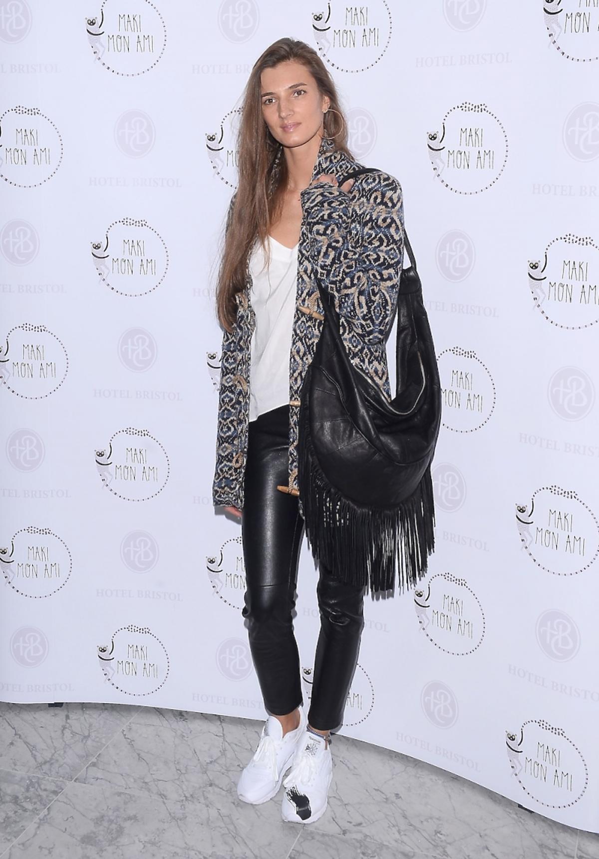 Kamila Szczawińska w skórzanych czarnych spodniach,  białych butach, czarnej torbie z frędzlami, białym topie, rozpinanym swetrze we wzory