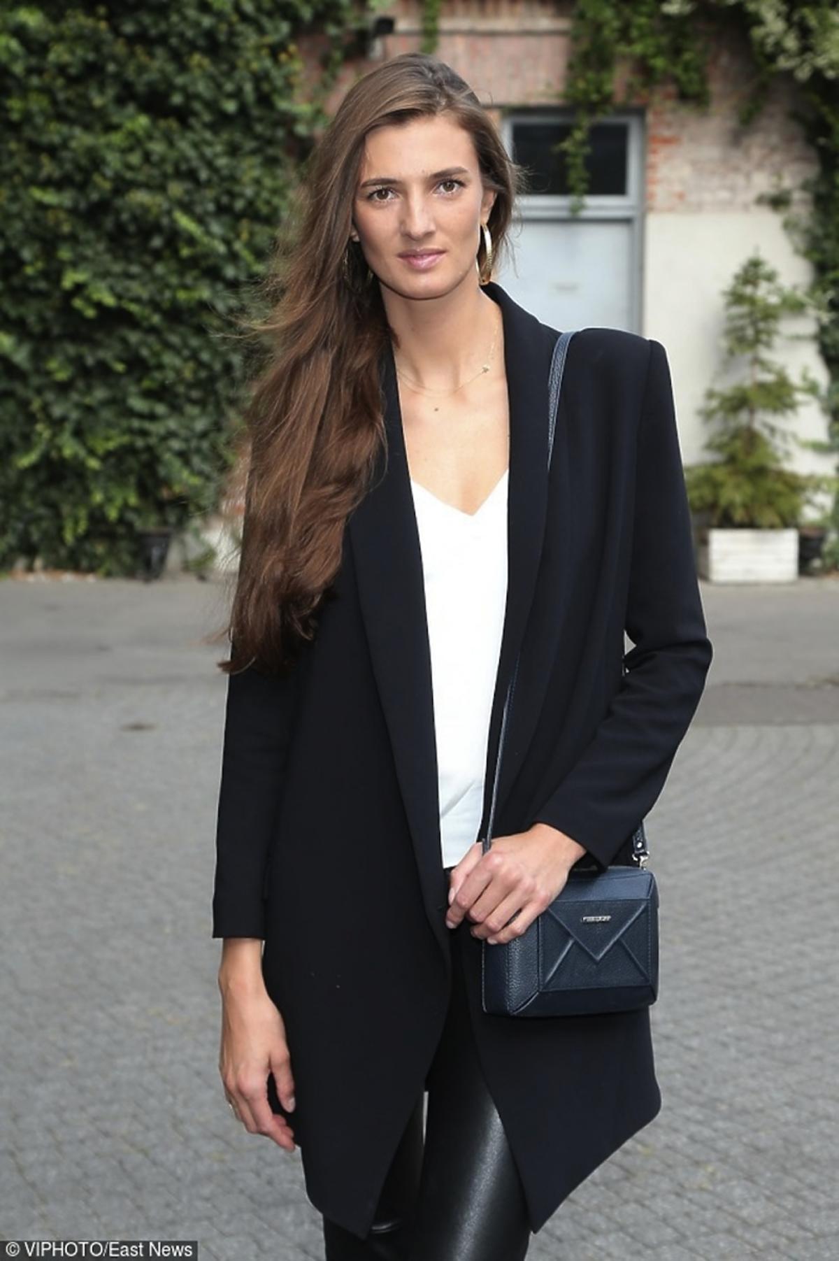 Kamila Szczawińska w skórzanych czarnych spodniach,  białych butach i, białym topie czarnej marynarce, niebiskiej torebce na pasku