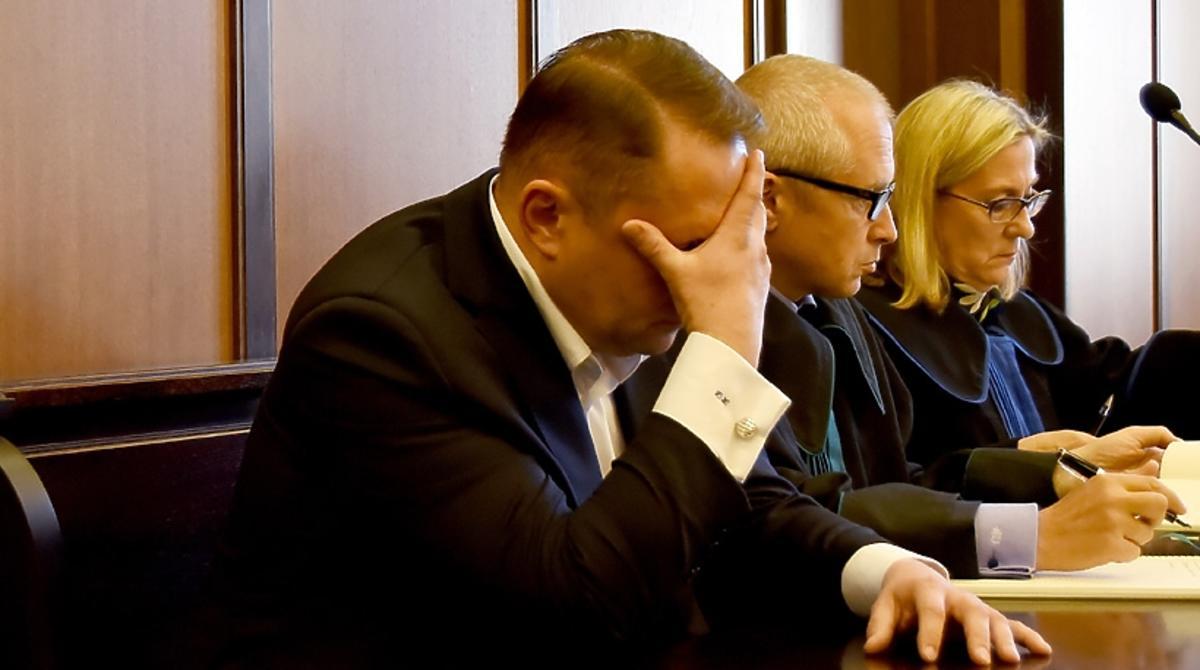Kamil Durczok na sali rozpraw zasłania twarz