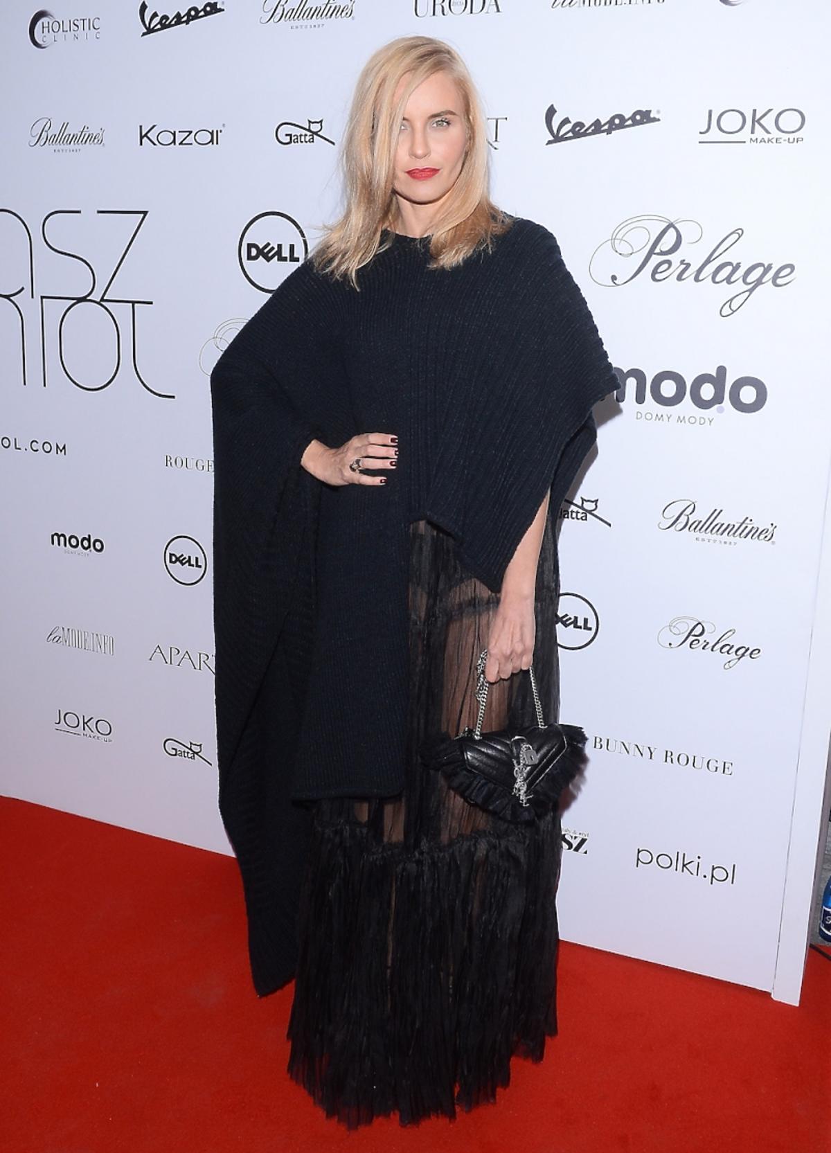 Joanna Horodyńska w czarnym ponczo, czarnej sukience z czarną torebką