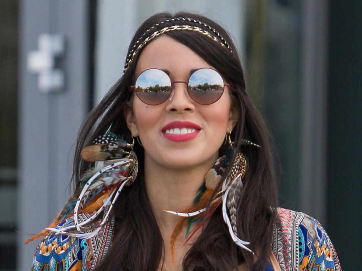 Macademian Girl w niebieskim topie, narzutka we wzory, spodnie w printy kolorowe, metaliczne niebieskie szpilki, okulary lenonki, paska etniczan, kolczyki z piórami