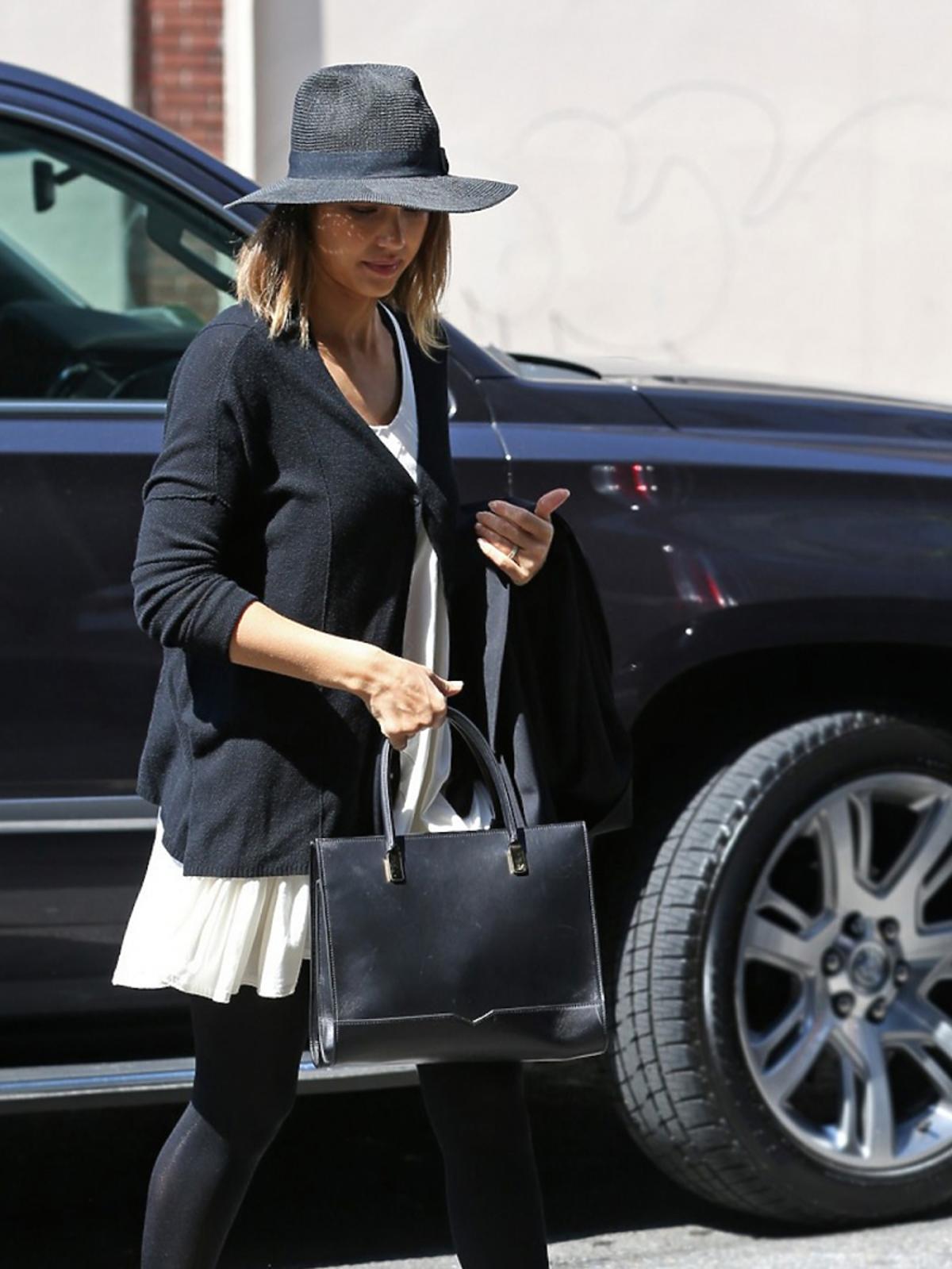 Jessica Alba w czarnym kapeluszu, swetrze , białej sukience, czarnio- białych butach na platformie