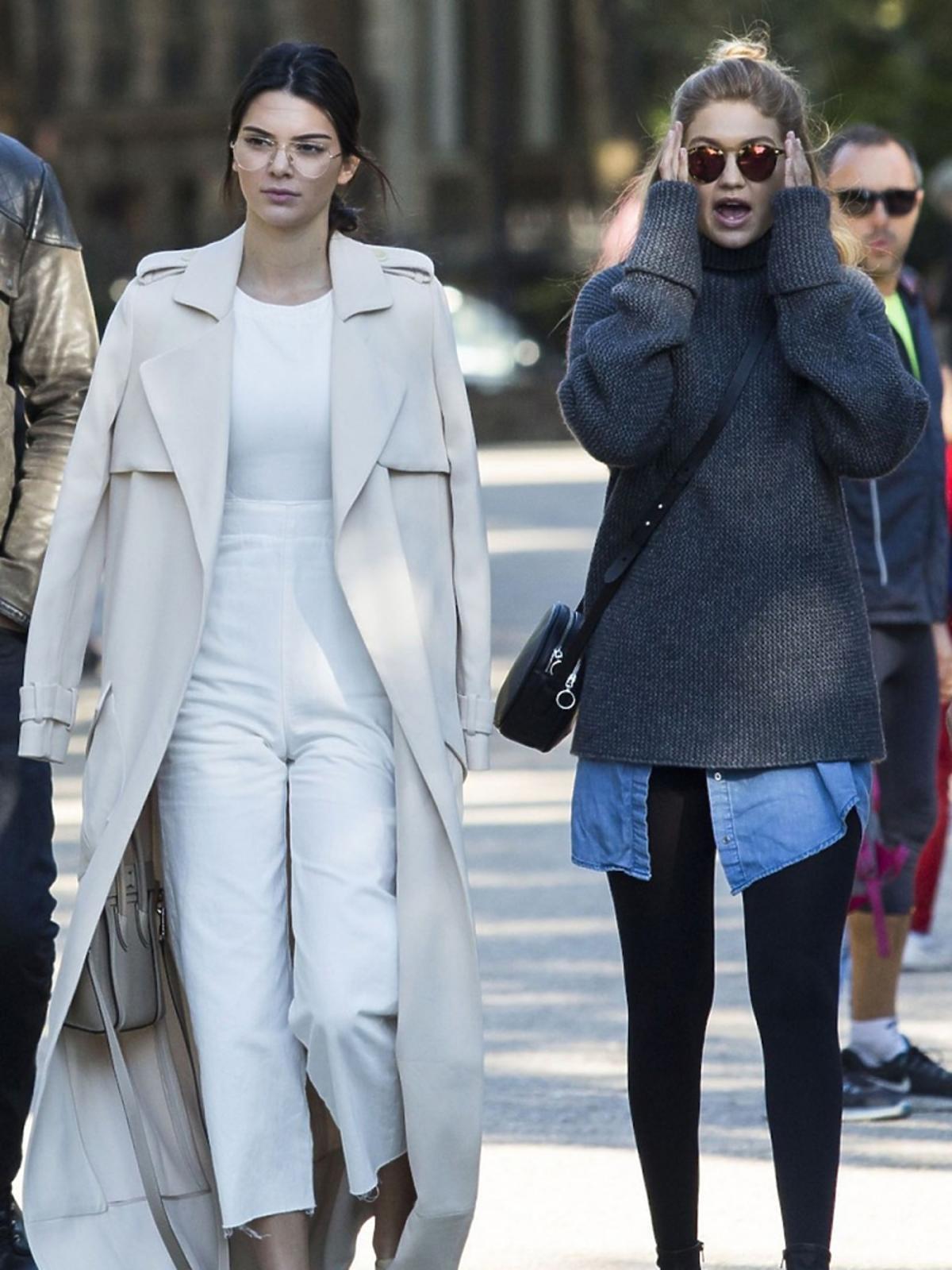 Kendall Jenner w beżowych płaszczu, białych spodniach i topie, beżowych butach z gwiazdkami, okularach