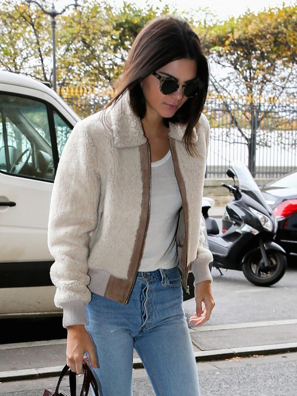 Kendall Jenner w dżinsach, białym topie, kożuszku krótkim, beżowych butach z gwiazdkami na drewniamym koturnie, okularach, brązowej torebie do ręki
