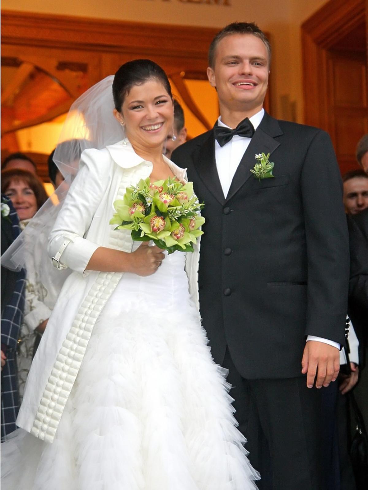 Katarzyna Cichopek w sukni ślubnej i Marcin Hakiel w garniturze jak wychodza z kościoła