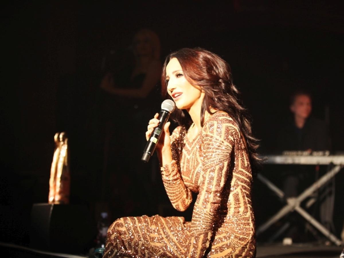 Justyna Steczkowska w cekinowej zlotej sukni siedzi na scenie i śpiewa