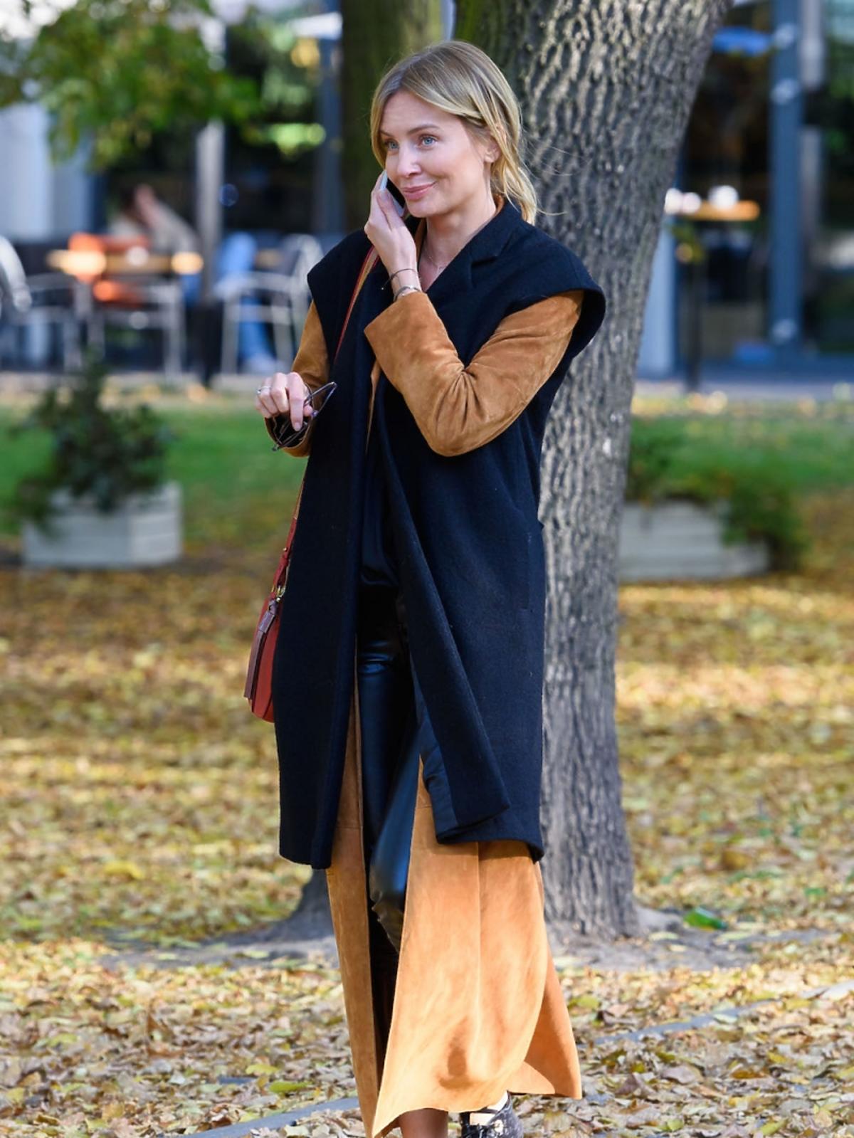 Agnieszka Szulim w zaszowym płaszczy, czarnej kamizelce, duzych okularach, czarne buty, czerwona torba