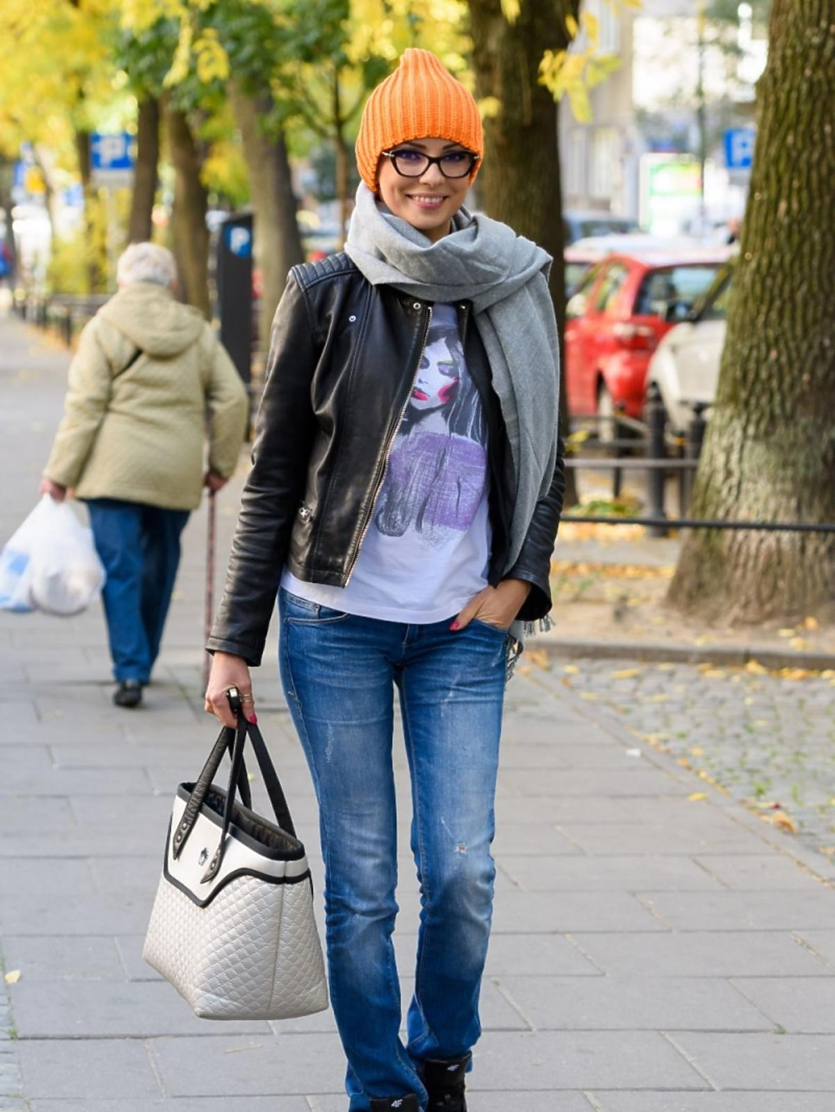 Dorota Gardias w szerokich dżinsach z białą torebką